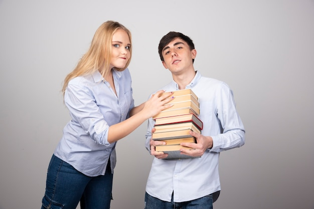 Donkerbruin kerelmodel dat een stapel boeken draagt dichtbij blondevrouw