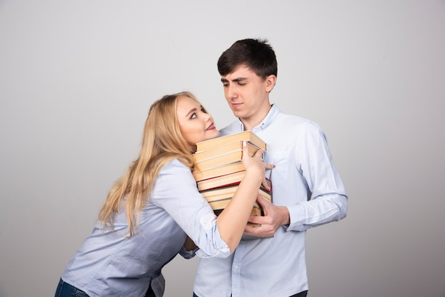 Donkerbruin kerelmodel dat staat en een stapel boeken draagt in de buurt van blonde vrouw