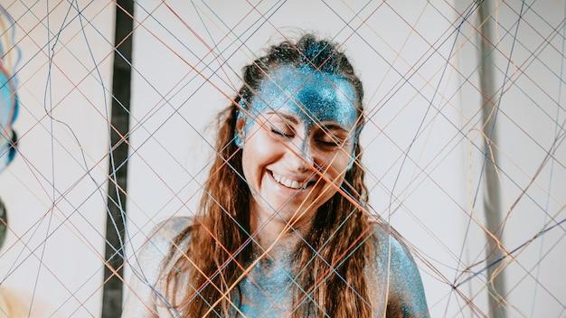 Donkerbruin meisje achter de netto draden. portret van mooie vrouw met blauwe fonkelingen op haar gezicht. het concept van mensen met individualiteit