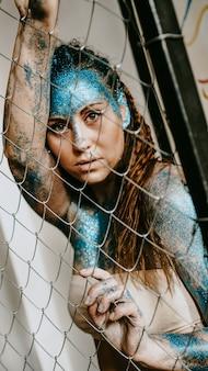 Donkerbruin meisje achter het net. portret van mooie vrouw met blauwe fonkelingen op haar gezicht. het concept van mensen met individualiteit