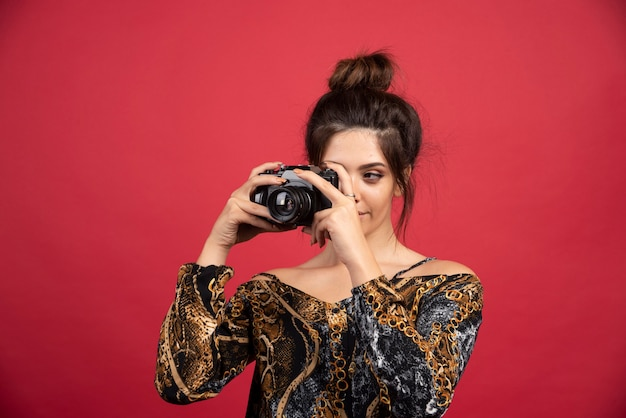 Donkerbruin meisje dat een professionele dslr-camera houdt en fotosessie doet.