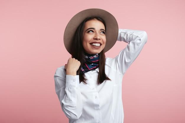 Donkerbruin meisje dat haar hoed houdt en over roze studiomuur glimlacht