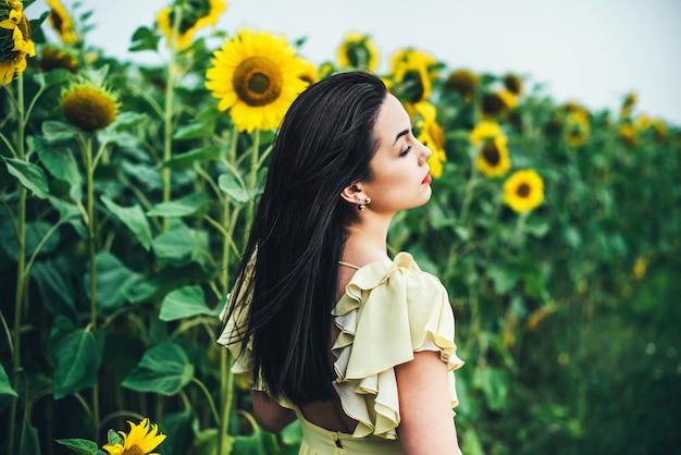 Donkerbruin meisje die openlucht dichtbijgelegen zonnebloemgebied ontspannen