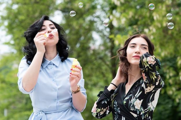 Donkerbruin meisje die zeepbels met vriend maken