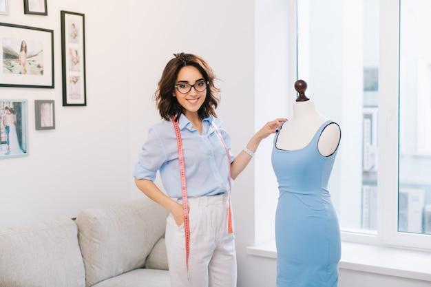 Donkerbruin meisje in blauw overhemd en witte broek die zich dichtbij een paspop in een workshopstudio bevinden. ze werkt met blauwe jurk. ze kijkt naar de camera.
