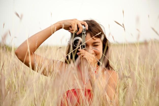Donkerbruin meisje met camera in weide.