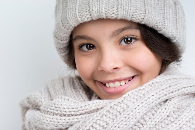 Donkerbruin meisje met een dikke halsdoek en een hoed