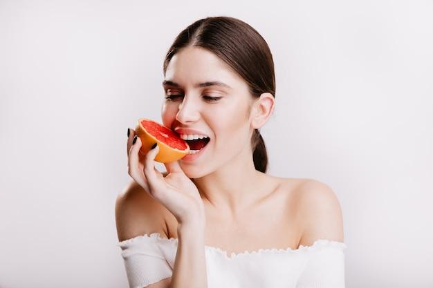 Donkerbruin meisje met een gezonde huid bijt sappige rode grapefruit. close-upportret van vrouw in goed humeur op geïsoleerde muur.