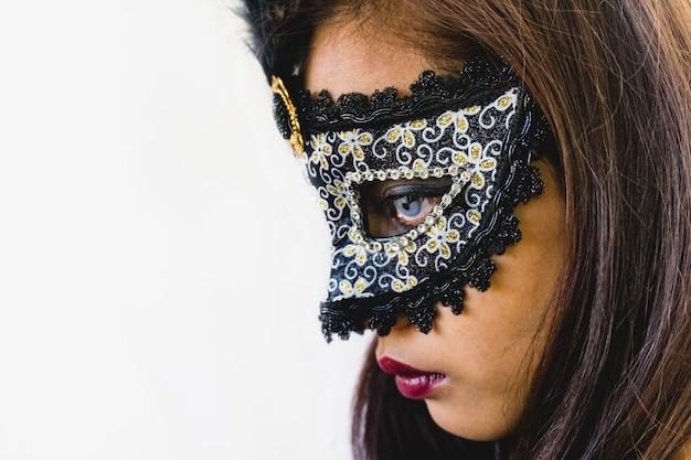 Donkerbruin meisje met een witte venetiaans masker