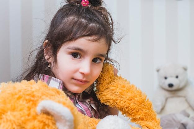Donkerbruin meisje met pluchestuk speelgoed