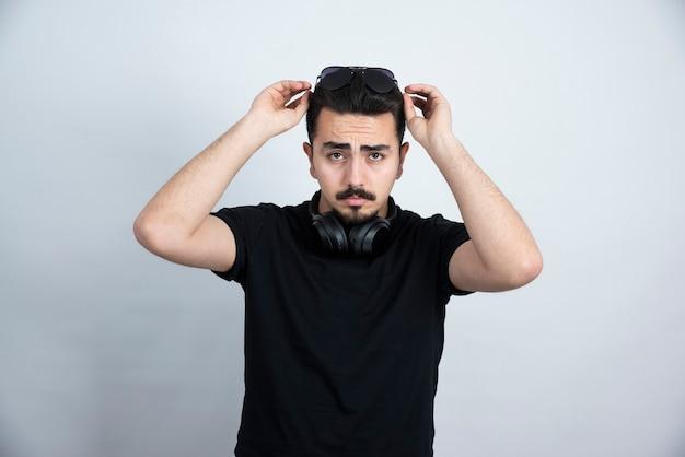 Donkerbruin mensenmodel dat zich in hoofdtelefoons bevindt en tegen witte muur stelt.