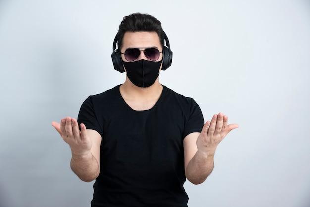 Donkerbruin mensenmodel in medisch gezichtsmasker dat hoofdtelefoons draagt.