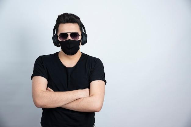 Donkerbruin mensenmodel met zonnebril die in medisch gezichtsmasker en hoofdtelefoons stellen.
