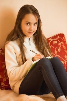 Donkerbruin tienermeisje dat in dagboek in slaapkamer schrijft