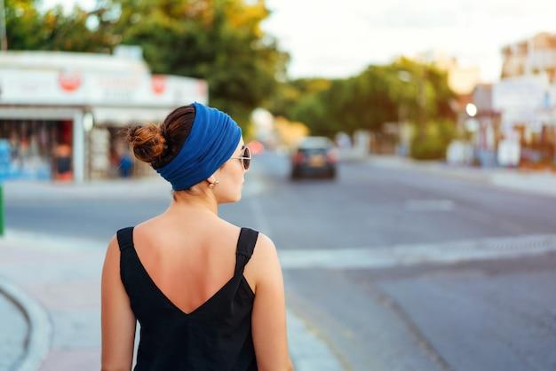 Donkerbruin toeristenmeisje die op de straat lopen