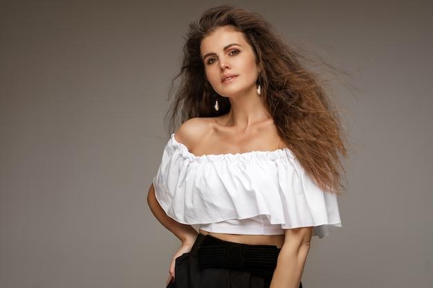 Donkerbruin wijfje dat witte blouse en zwarte rok draagt