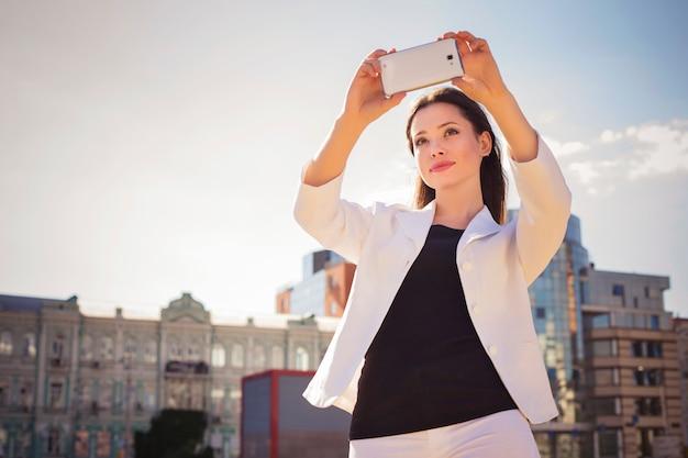 Donkerbruine bedrijfsvrouw die in wit kostuum selfie op een tablet in haar handen in openlucht fotograferen. kopieer ruimte