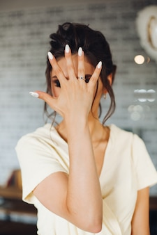 Donkerbruine bruid die hand met trouwring tonen en gezicht verbergen.