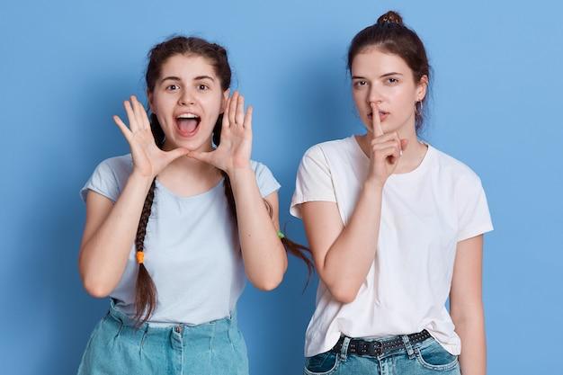 Donkerbruine dame met haarknotje weigert te luisteren naar de huil van haar vriend en houdt de vinger bij de lippen