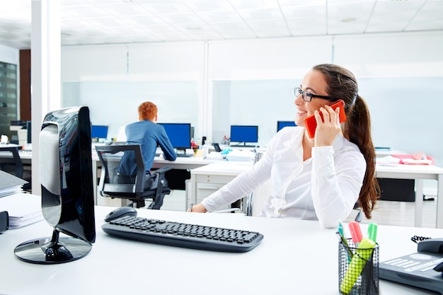 Donkerbruine glazenonderneemster die in bureau werken