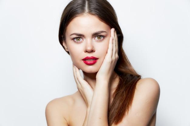 Donkerbruine heldere naakt schouders rode lippen charmeren handen op gezichtsmake-up