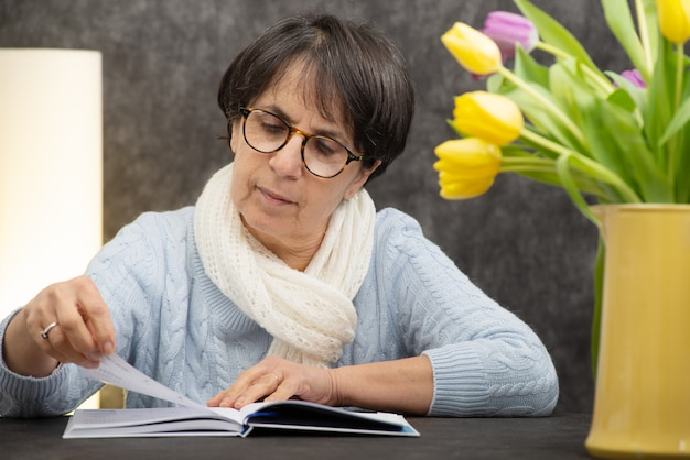 Donkerbruine hogere vrouw die met glazen boek leest