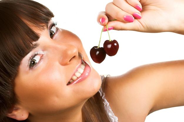 Donkerbruine holding cherryes, sluit omhoog, bekijkend camera, studio op wit