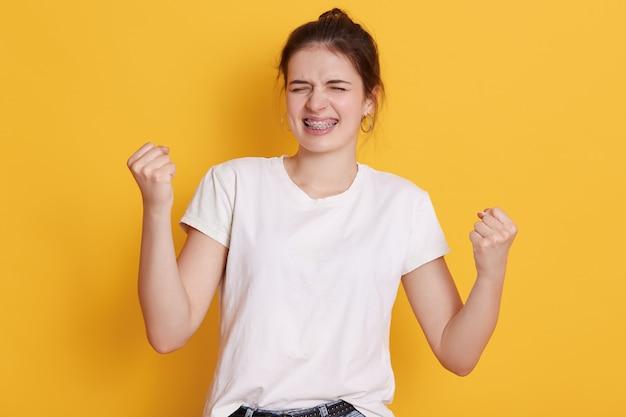 Donkerbruine jonge aantrekkelijke jonge vrouw die vuisten dichtklemmen en glimlachen, die haar succes vieren