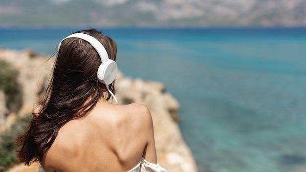 Donkerbruine jonge vrouw die aan muziek luistert