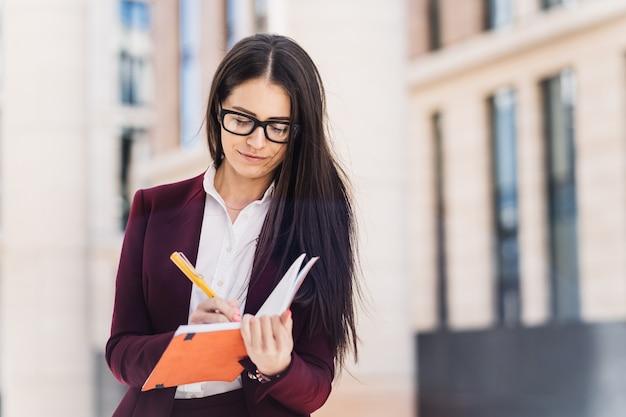 Donkerbruine jonge vrouw die in glazen in haar notitieboekje schrijft