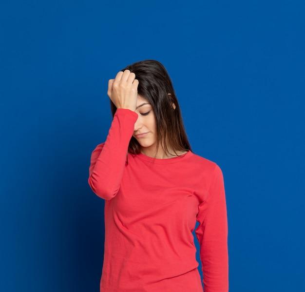 Donkerbruine jonge vrouw die over blauwe muur gesturing