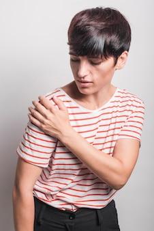 Donkerbruine jonge vrouw die schouderpijn heeft die over witte achtergrond und wordt geïsoleerd