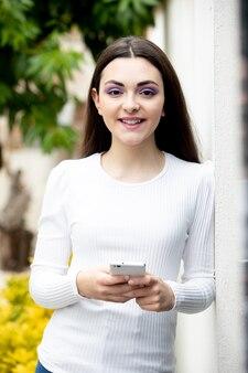 Donkerbruine jonge vrouw met een slimme telefoon buiten