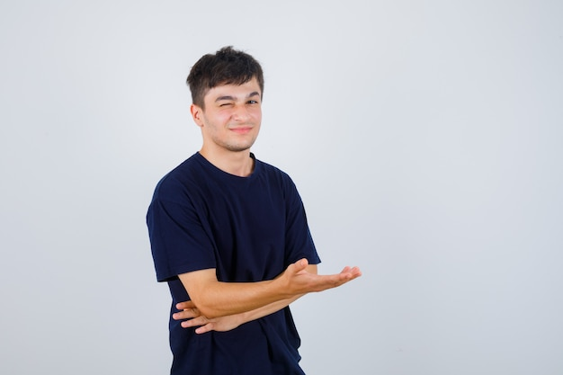 Donkerbruine man die iets in t-shirt beweert te laten zien en vrolijk, vooraanzicht kijkt.