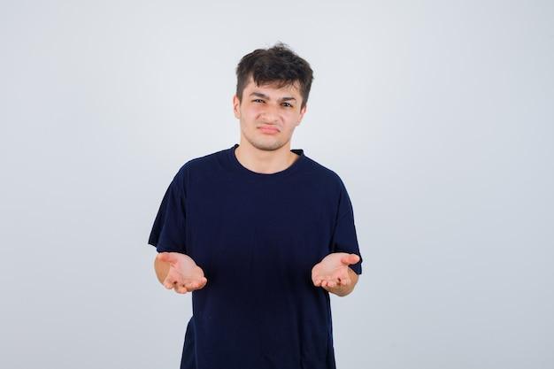 Donkerbruine man die met domme vraag in donker t-shirt ontevreden is en somber, vooraanzicht kijkt.