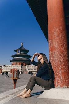 Donkerbruine meisjeszitting op de stappen door tempel van heven in china