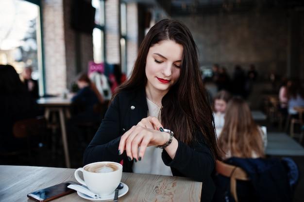 Donkerbruine meisjeszitting op koffie met kop van cappuccino en het bekijken haar horloges bij de hand.