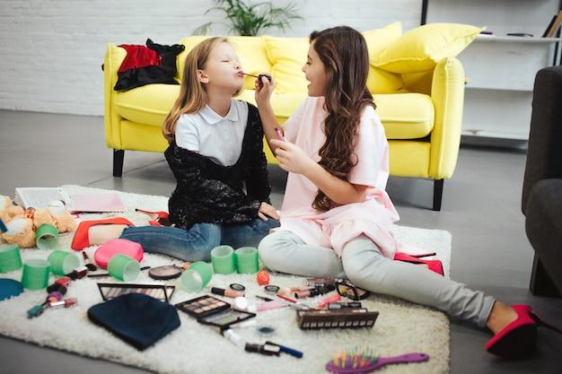 Donkerbruine meisjeszitting op tapijt in ruimte met haar vriend en het zetten van lippenstift op haar lippen. blonde tiener geconcentreerd.