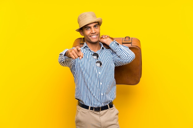 Donkerbruine mens die een uitstekende aktentas over geïsoleerde gele verrast achtergrond houdt en voorzijde richt