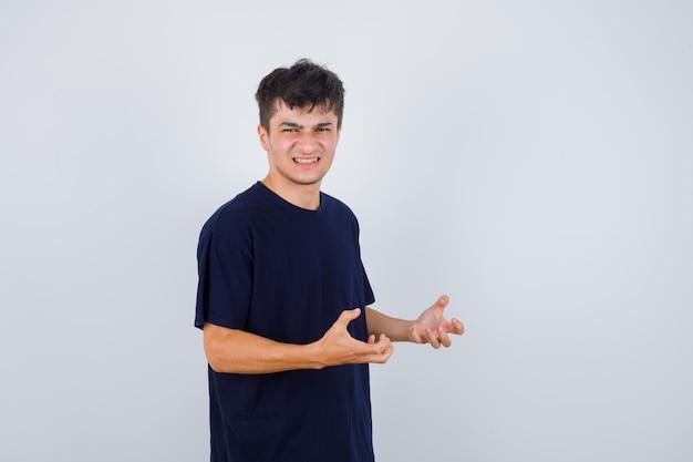 Donkerbruine mens die handen op agressieve manier in t-shirt houdt en gestrest, vooraanzicht kijkt.