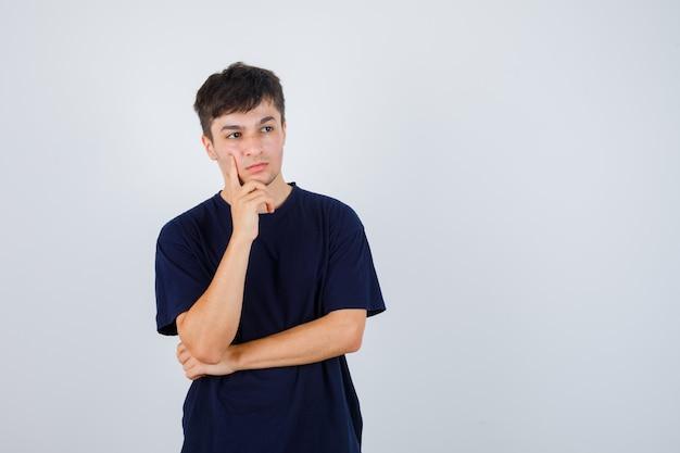 Donkerbruine mens die zich in denken stelt in donker t-shirt en ernstig, vooraanzicht kijkt.