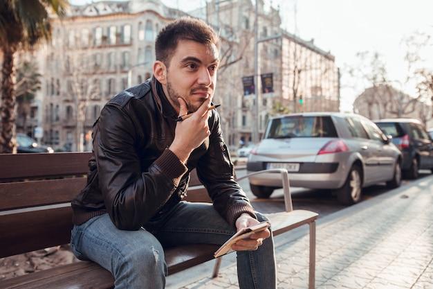 Donkerbruine mens met baard die en in notitieboekje schrijft denkt