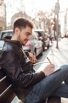 Donkerbruine mens met baard die in notitieboekje schrijft