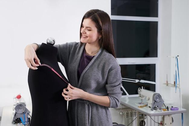 Donkerbruine naaister die zwart model in workshop meten, het werk van de kleermakersstudio