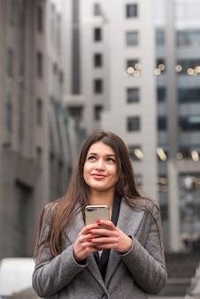 Donkerbruine onderneemster die haar smartphone gebruikt
