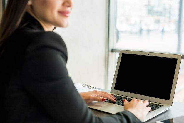 Donkerbruine onderneemster die laptop met behulp van