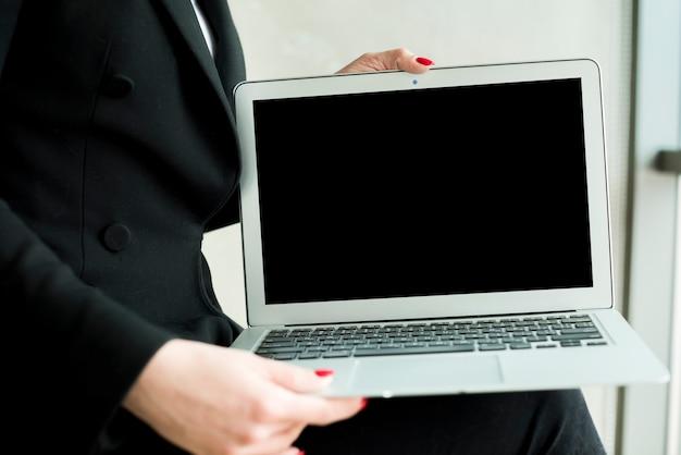 Donkerbruine onderneemster die laptop toont