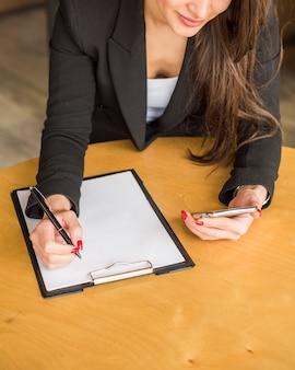 Donkerbruine onderneemster die op een document schrijft