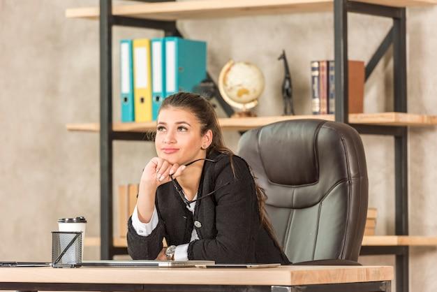 Donkerbruine onderneemster die op haar kantoor denkt