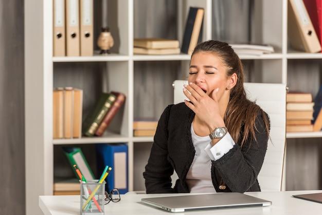 Donkerbruine onderneemster die op haar kantoor geeuwt